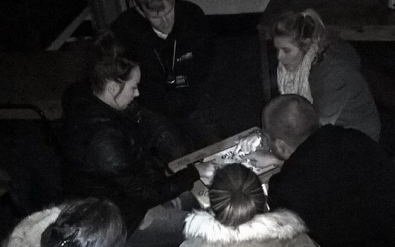 group of people using ouija board